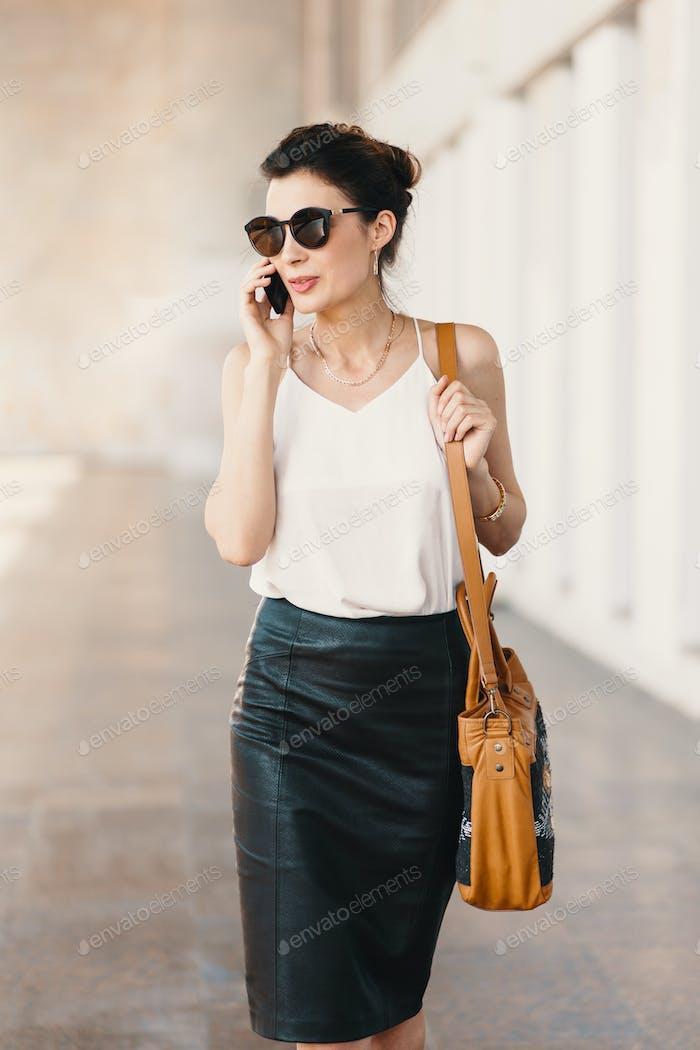 Exquisite Business-Frau in Lederrock und Seidenbluse sprechen am Telefon im Freien
