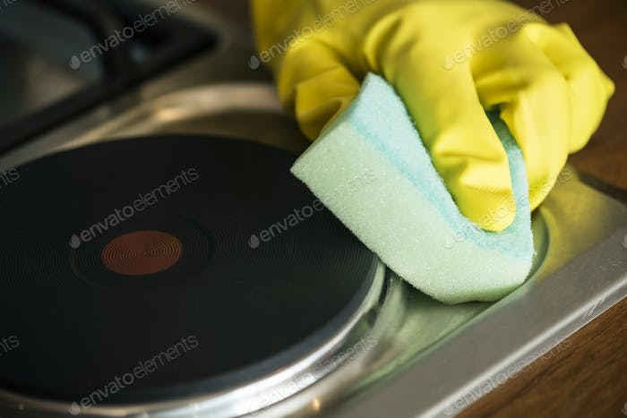Closeup of hands wearing gloves wiping the stove domestic chores concept