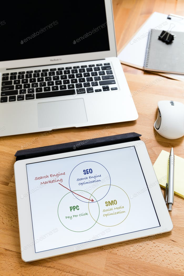 Business working desk with tablet showing search engine marketing concept