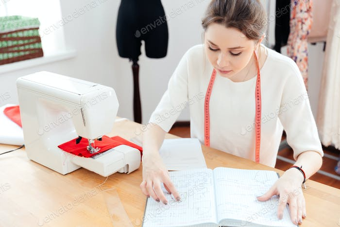 Serious woman seamstress thinking and reading notes in notebook