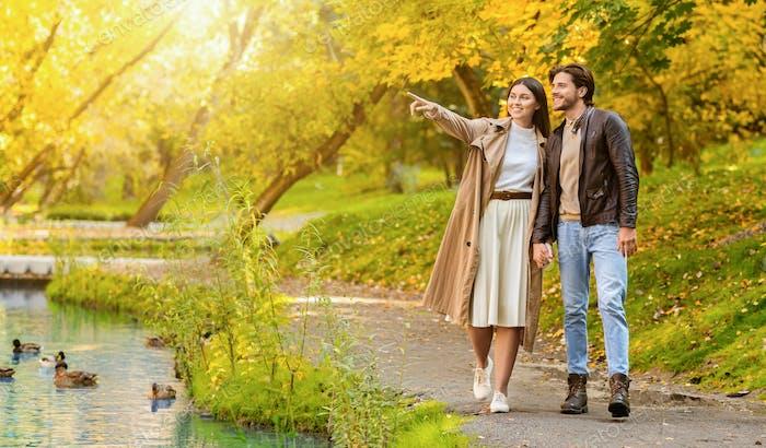 Paar genießen Herbst Wald, Frau zeigt auf leeren Raum