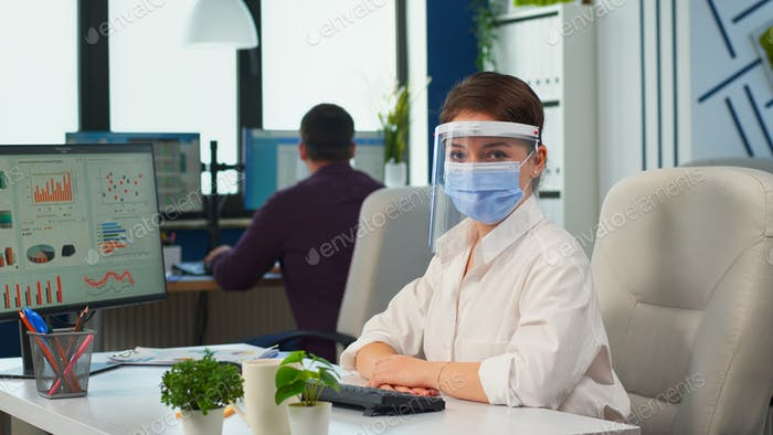 Manager woman with visor and protection mask looking at camera