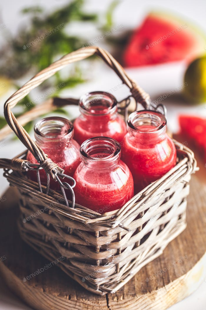 Watermelon juice in jars with a basket with mint leaves and lime citrus