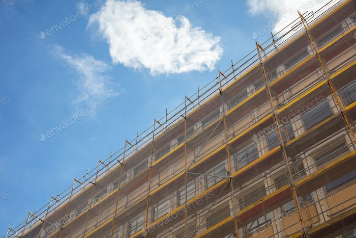 Building construction with scaffolding, blue sky background