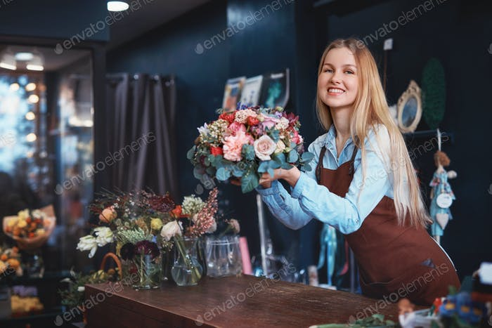 Smiling girl in a flower shop