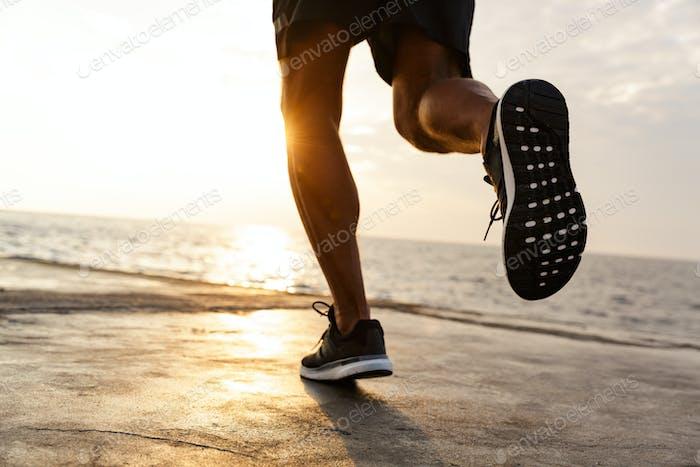 Gekürzte männliche Beine von gesunden Sportler tragen Shorts und schleichen
