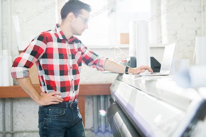 Man using laptop in publishing office