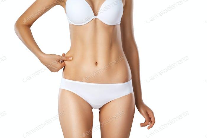 Unrecognizable woman in underwear testing fat layer on waist