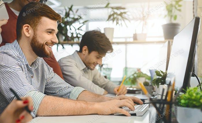 Smiling man enjoying work in modern comfortable office