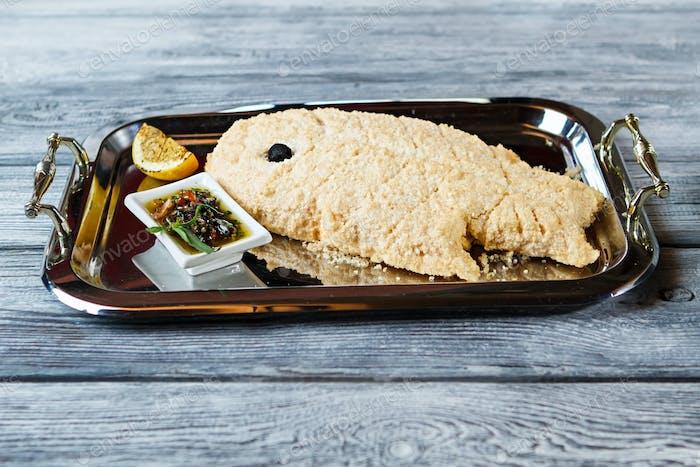 Breaded fish on tray
