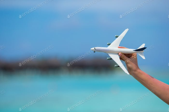 Little white toy airplane on background of turquoise sea