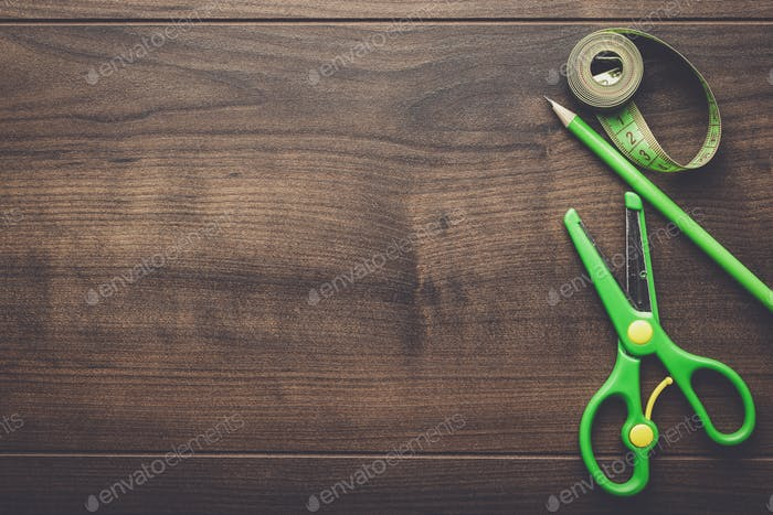 green measuring tape, scissors and pencil