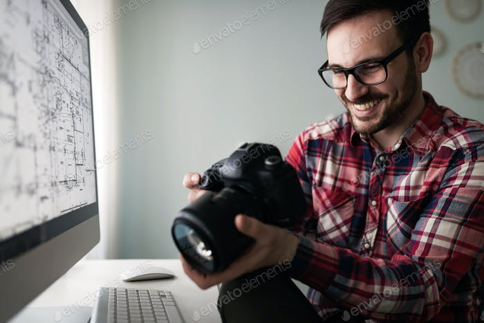Young handsome designer working on project on computer