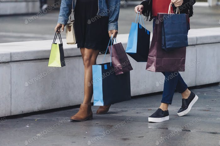two female friends doing shopping downtown, full of shopping bags