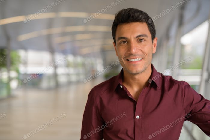 Face of happy Hispanic businessman smiling on the footbridge