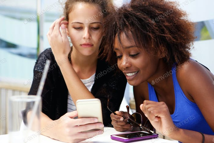Two girl friends looking at cellphone