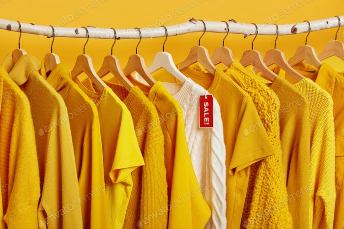 Clearance sale in clothes store. Yellow and bright clothing on hangers during Black Friday. Big disc