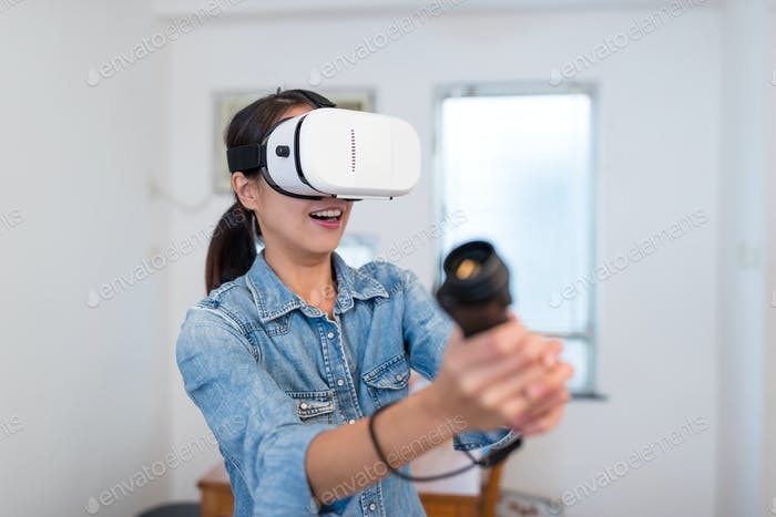 Thrilled Woman play game with virtual reality device at home