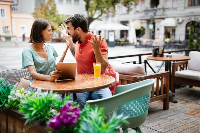 Young couple arguing in cafe. People, cheating, conflict, relationship problems concept