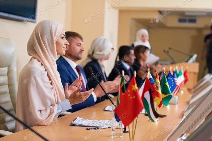 Young female delegate in hijab and her foreign colleagues applauding