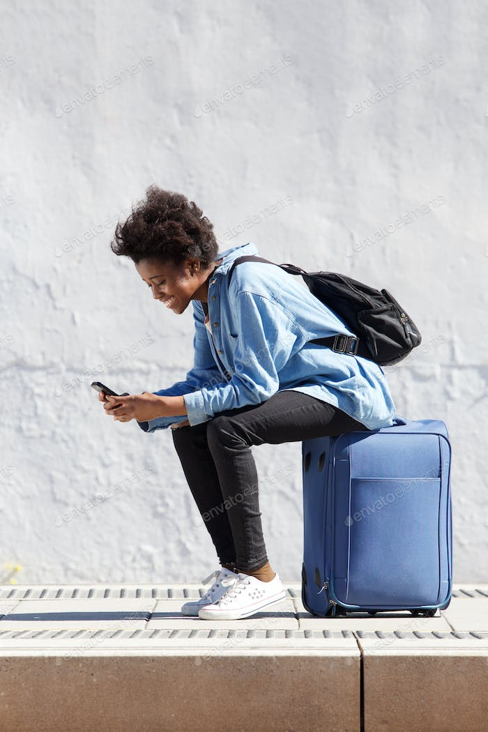young african woman sitting on suitcase using mobile phone