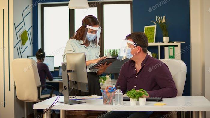 Businessman with visor pointing on desktop explaining graphs