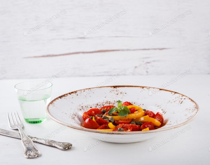 Warm salad with cherry tomatoes,sweet peppers and capers.