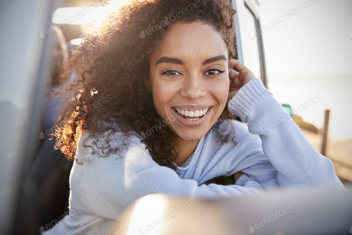 Young woman leaning on open window of car looking to camera