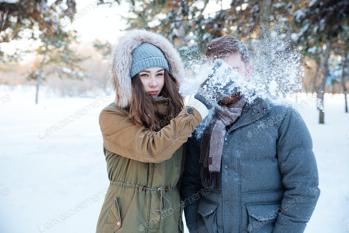 Amusing woman thowing snowball in her boyfriend face