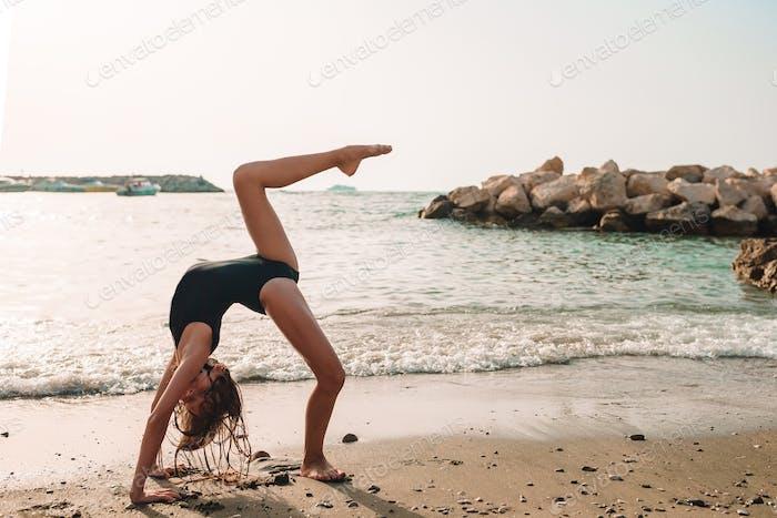 Aktives kleines Mädchen am Strand mit viel Spaß. Niedlich Kind machen sportliche Übungen auf der Küste