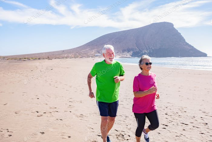 couple of active seniors or pensioners doing exercise together at the beach running and jogging