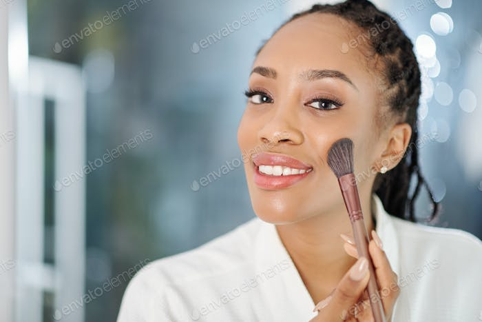 Woman applying peach blush