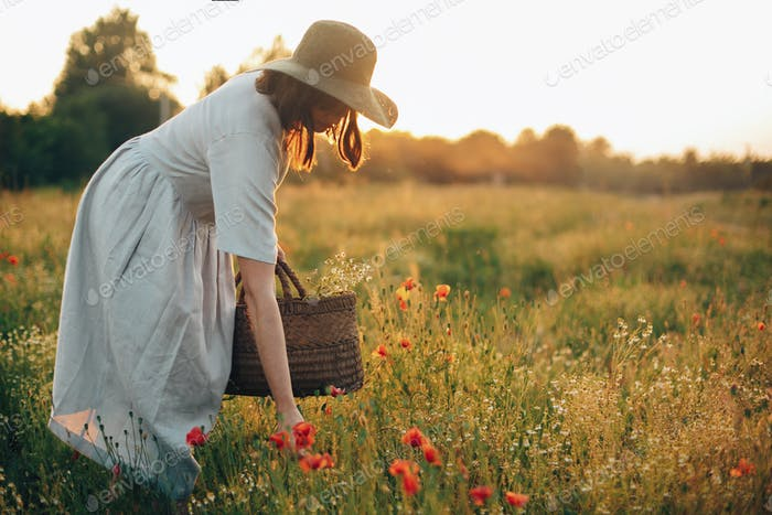 Stylish girl in linen dress gathering flowers in rustic straw basket