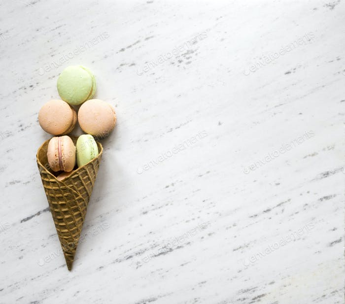 Colorful macaron in ice cream cone of waffle on marble backgroun