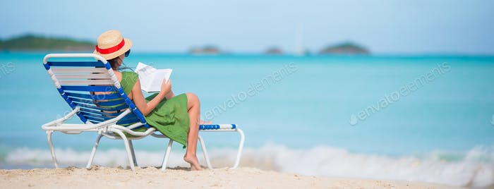 Young woman reading book on chaise-lounge on the beach