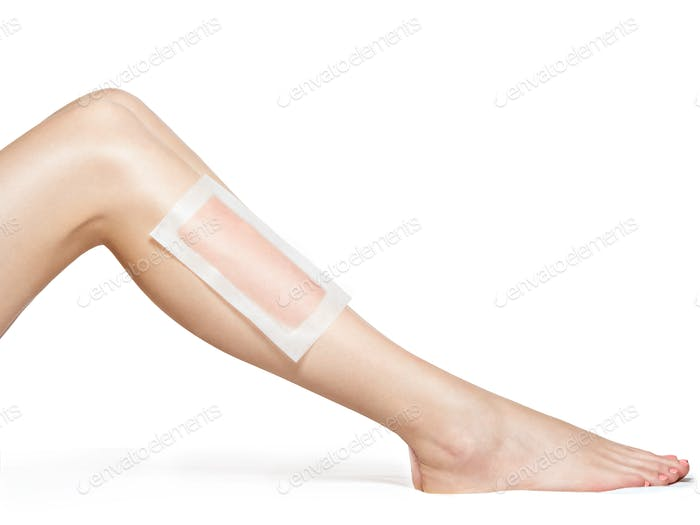 woman depilating legs by waxing