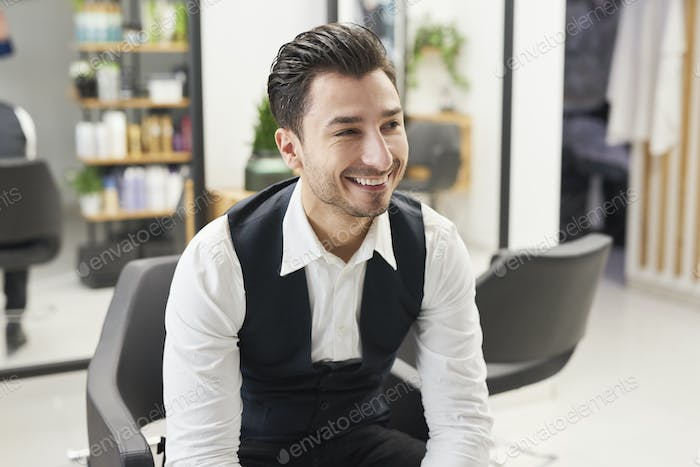 Smiling barber sitting in hair salon