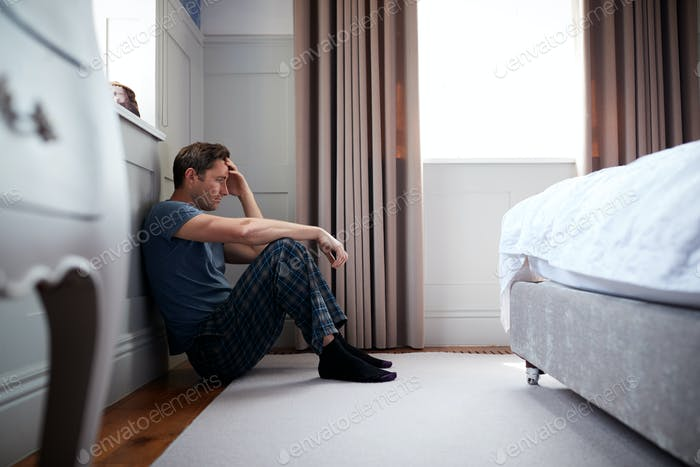 Depressed Man Wearing Pajamas Sitting On Floor Of Bedroom