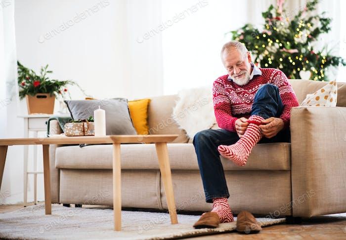 A senior man putting socks on at home at Christmas time.
