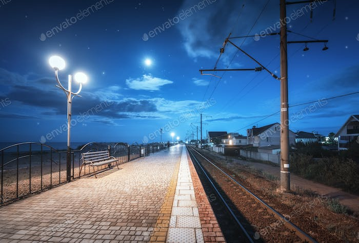 Railway station at night in summer. Starry sky over railroad
