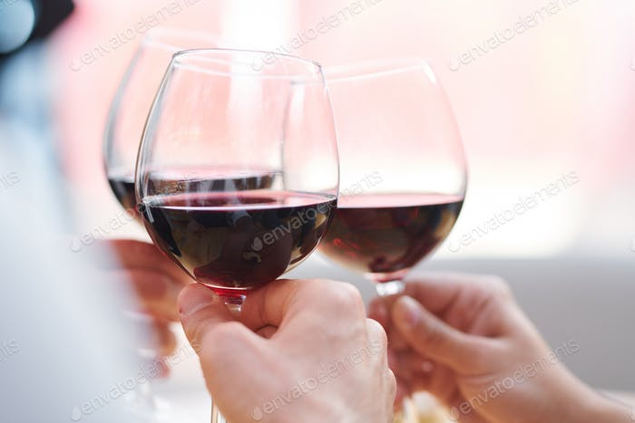 Three wineglasses with red cabernet held by toasting friends