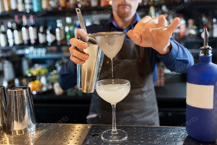 barman with shaker preparing cocktail at bar