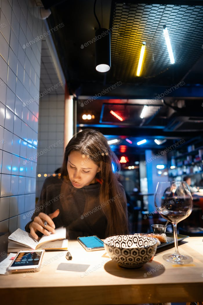 Woman works at a cafe in the evening