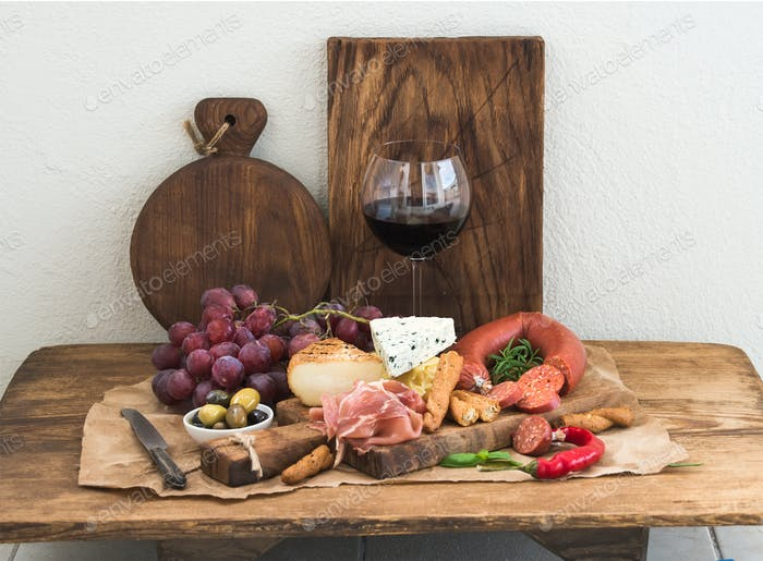 Glass of red wine, cheese and meat board, grapes,fig, strawberries, honey, bread sticks