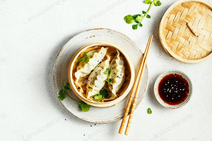 Vegetables dumplings Dim Sum in bamboo steamer on a grey background with copy space. Asian cuisine