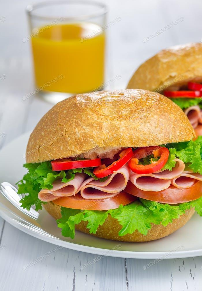 Gesunde Sandwiches mit Schinken und einem Glas Orangensaft