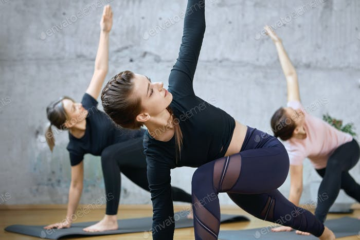 Crop of fitnesswomen practicing stretching on mats