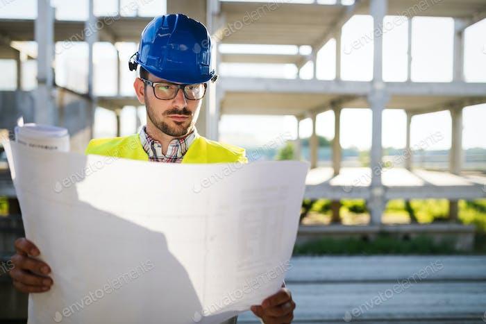 Bauingenieur in Hardhat mit Projekt in Händen