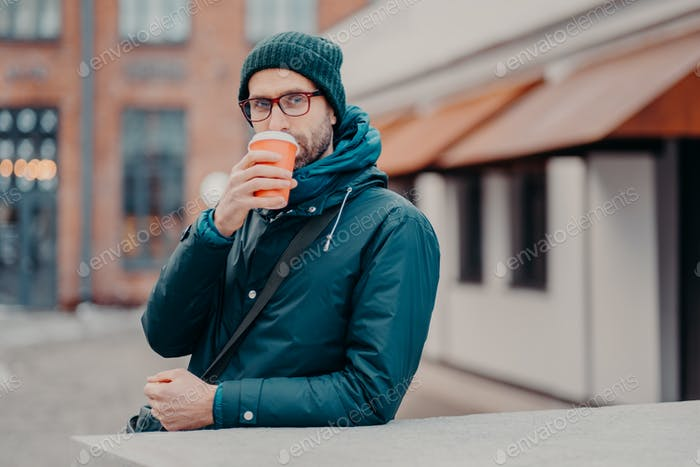 Handsome hipster drinks takeaway coffee from disposable cup, dressed in headgear, jacket