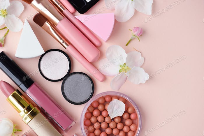 Makeup brush and decorative cosmetics with apple blossom on pink